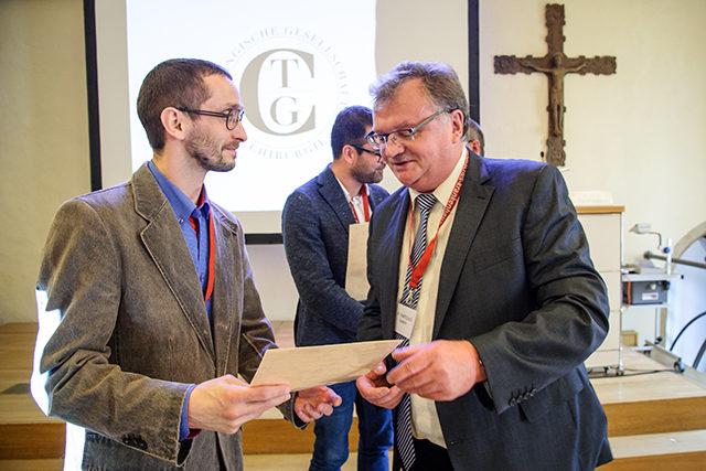 Dr. med. Herry Helfritzsch übergibt die Siegerurkund für den zweiten Platz des Jungen Forums an Oleksandr Pustovoyt
